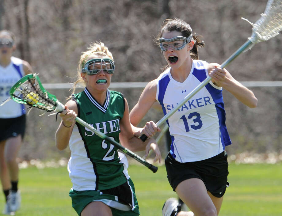 Shen's Lisa Bodah(l) tries to make it passed Shakers Caroline Rehfuss(r) in a league Lacrosse match at the Shaker High School field in Latham, New York April 17, 2009. (Skip Dickstein / Times Union) Photo: SKIP DICKSTEIN / 00003463A
