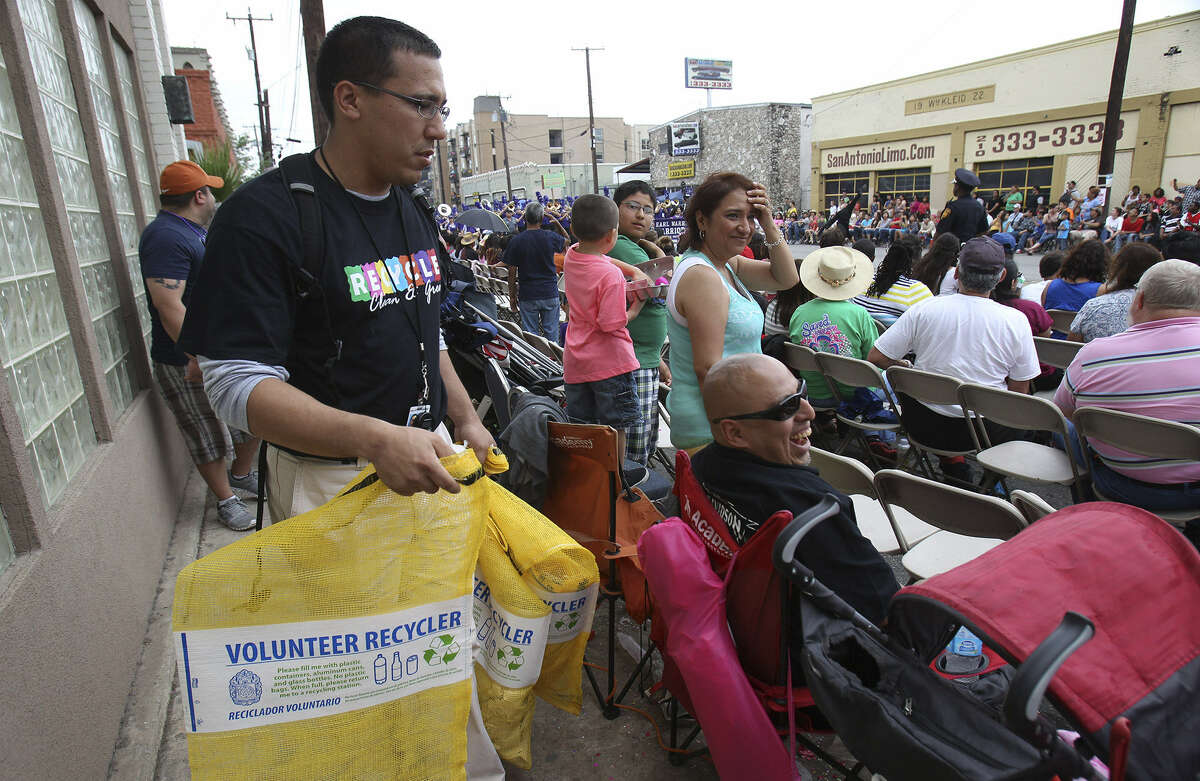 A city staffer distributes recycling bags. The Battle of Flowers and Flambeau parades have a recycling rate of 17 percent.