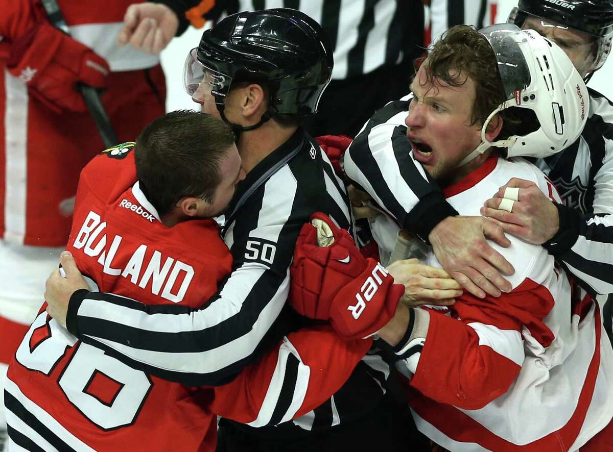 The Blackhawks' Dave Bolland (left) tussles with the Red Wings' Justin Abdelkader during Game 1 of their Western Conference semifinal. Chicago has beaten Detroit eight straight times.