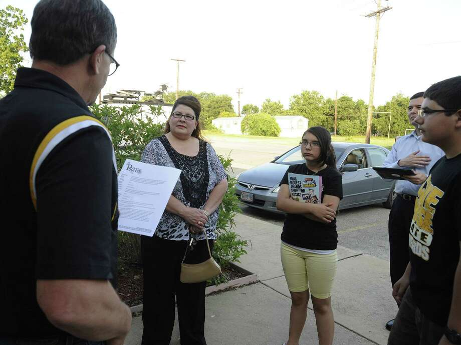 Christina Mercado (second from left) listens as Randy Ewing, a Lytle ISD spokesman (left) announces that Mercado's 1-0 victory in Saturday's school board election will stand.