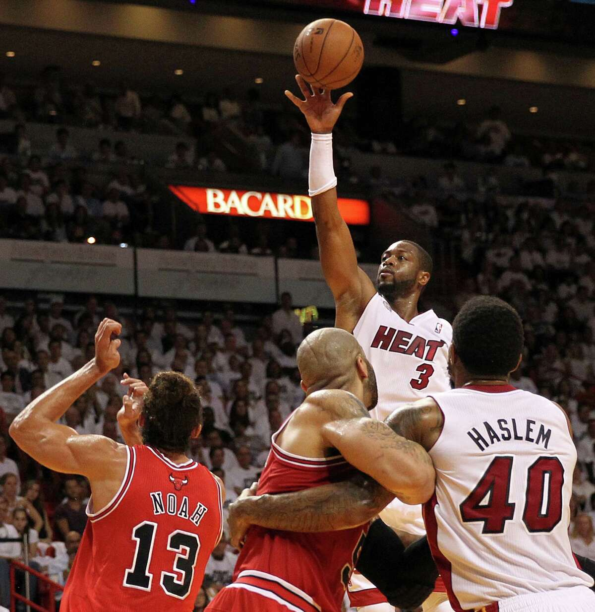 The Heat's Dwyane Wade shoots over the Bulls' defense during the third quarter. Wade, playing on a sore right knee, finished with 18 points.