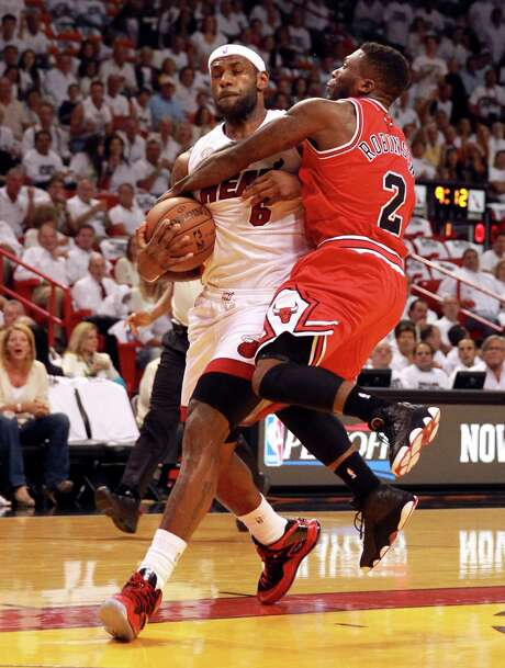 Giving up nearly a foot, the Bulls' Nate Robinson decides hanging on is the best way to try to stop LeBron James. Photo: CHARLES TRAINOR JR, MBR / Miami Herald