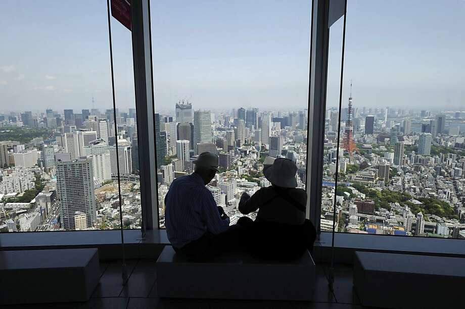 A couple views the skyline from the observation deck at the Roppongi Hills Mori Tower, operated by Mori Building Co., in Tokyo, Japan, on Wednesday, May 15, 2013. Japan's economy expanded the most in a year last quarter as consumer spending and export gains outweighed the weakest business investment since the wake of the March 2011 earthquake and tsunami. Photographer: Akio Kon/Bloomberg Photo: Akio Kon, Bloomberg