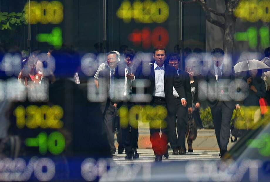 Pedestrians are reflected on a quotation board of the Tokyo Stock Exchanges in Tokyo on May 16, 2013. The benchmark Nikkei 225 index, which closed at its highest level in more than five years on May 15, was up 50.02 points to 15,146.05 at the start.    AFP PHOTO / KAZUHIRO NOGIKAZUHIRO NOGI/AFP/Getty Images Photo: Kazuhiro Nogi, AFP/Getty Images