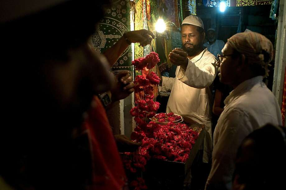 A flower-seller sells garlands of flowers to devotees near a Sufi shrine as pilgrims transit through the city on their way to the annual Urs in Ajmer, in New Delhi on May 12, 2013. Thousands of devotees from different parts of the country travel to the 801st annual Urs of Khwaja Moinuddin Chishti, commemorating the death anniversary of the Sufi saint, which officially began on the night of May 11.   AFP PHOTO/ Anna ZIEMINSKIANNA ZIEMINSKI/AFP/Getty Images Photo: Anna Zieminski, AFP/Getty Images