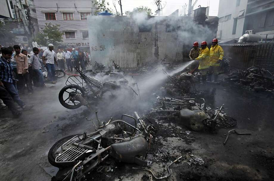 Indian firemen spray water on motorbikes that were gutted in a fire accident in Hyderabad, India, Wednesday, May 15, 2013. Around 25 vehicles were destroyed in a fire caused by a blast in an electrical transformer. No casualties or injuries were reported. (AP Photo/Mahesh Kumar A.) Photo: Mahesh Kumar A, Associated Press