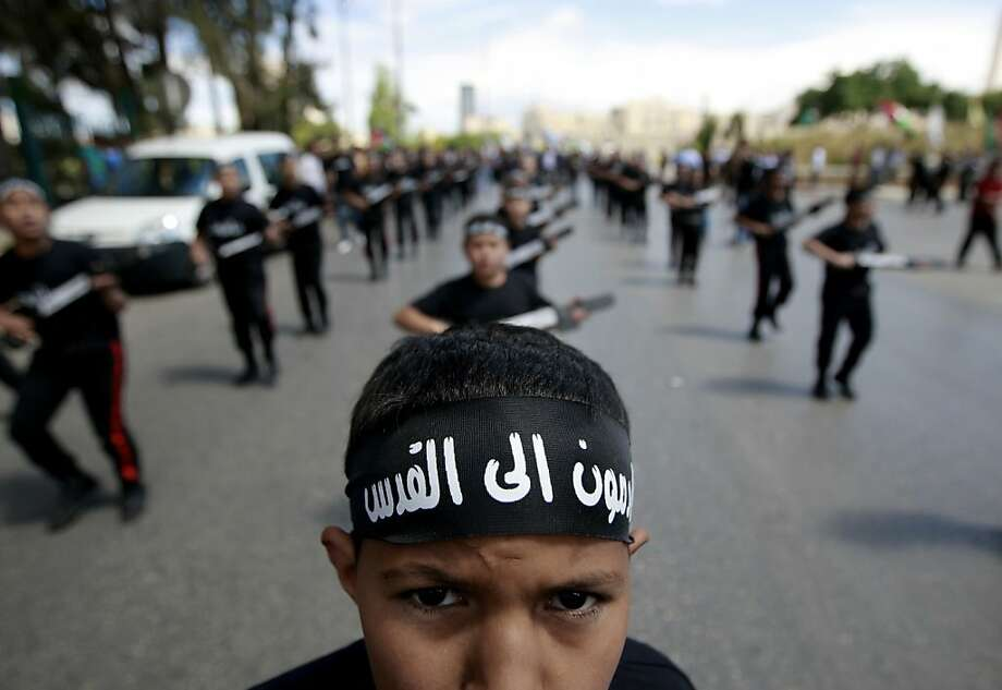 "A Palestinian boy wears a bandana which in Arabic that reads, ""coming to Jerusalem,"" during a rally to mark the Nakba Day in the West Bank town of Rramallah, Wednesday, May 15, 2013., Tuesday, May 14, 2013. Palestinians annually mark the ""nakba,"" or ""catastrophe"" — the term they use to describe their defeat and displacement in the war that followed Israel's founding in 1948. (AP Photo/Majdi Mohammed) Photo: Majdi Mohammed, Associated Press"