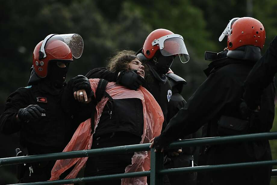 Basque police detain alleged member of the Basque armed group ETA, Urtza Alkorta, wearing pink plastic on her body, as she stands on a bridge with some hundreds of her supporters, in Ondarroa, northern Spain on Wednesday, May 15, 2013.  More than three hundred policemen participated in the operation to detain Alkorta to answer allegations by the National Court accusing her of involvement with the armed separatist group ETA.(AP Photo/Alvaro Barrientos) Photo: Alvaro Barrientos, Associated Press
