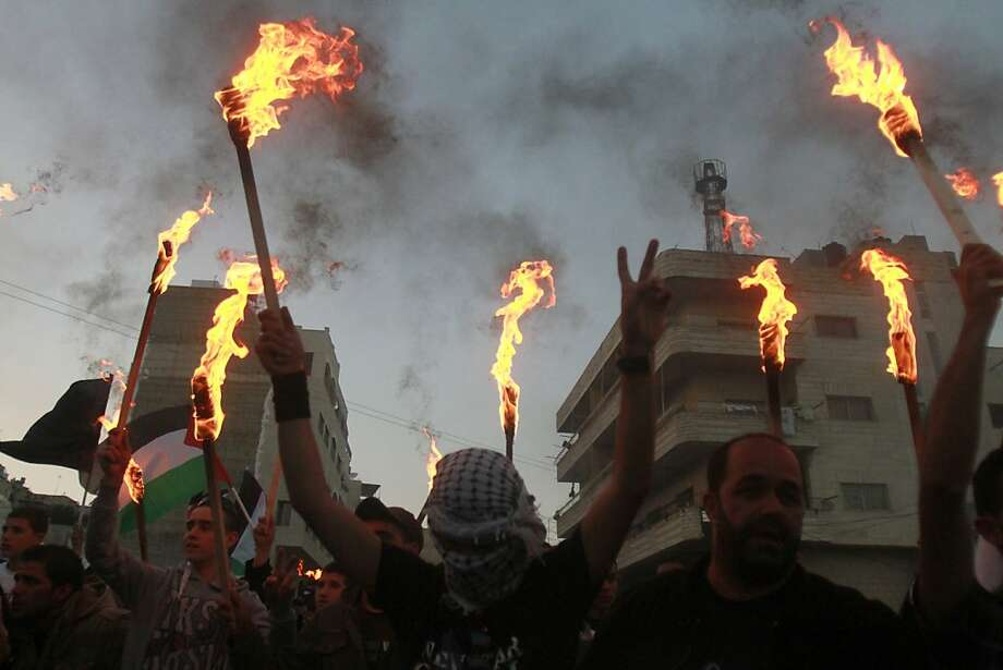 """TOPSHOTS Palestinian protestors hold up torches during a rally to commemorate the 1948 creation of Israel known in Arabic as the """"Nakba"""" (catastrophe)  in the West Bank city of Bethlehem on May 14, 2013. Palestinians are preparing to mark Nakba day on May 15 which commemorates the exodus of hundreds of thousands of their kin after the establishment of Israel state.  AFP PHOTO/MUSA AL-SHAERMUSA AL-SHAER/AFP/Getty Images Photo: Musa Al-shaer, AFP/Getty Images"""