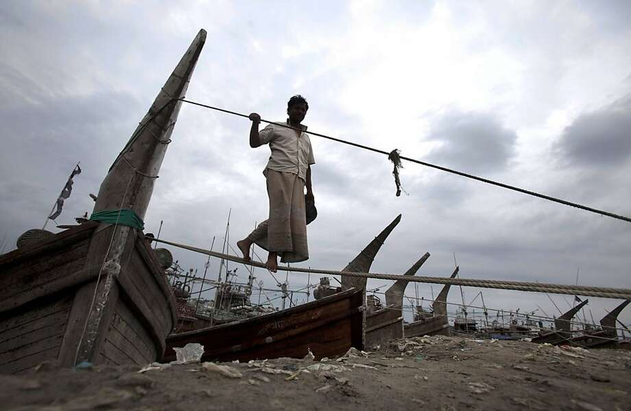 A Bangladeshi fisherman uses an anchored ropes of his boat to come on the banks of the river Kornofuli, in Chittagong, Bangladesh, Wednesday, May 15, 2013. Cyclone Mahasen is expected to make landfall early Friday. The storm was heading toward Chittagong, Bangladesh, but could shift east and deliver a more direct hit on Rakhine state in Myanmar. (AP Photo/ A.M.Ahad) Photo: A.M. Ahad, Associated Press