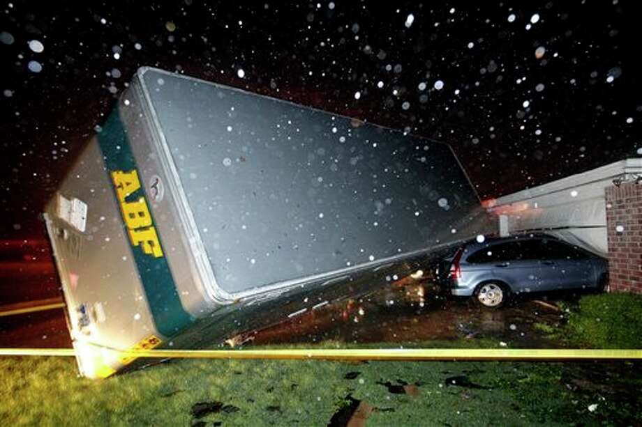A trucking company trailer landed on a car that was parked in front of a Lindsey Ln. home in Cleburne Texas after a powerful storm went through Wednesday night, May 15, 2013. Neighbors say the trailer was parked on the street and was rolled over onto the car. (AP Photo/The Dallas Morning News, Tom Fox) Photo: Tom Fox, Associated Press / Dallas Morning News