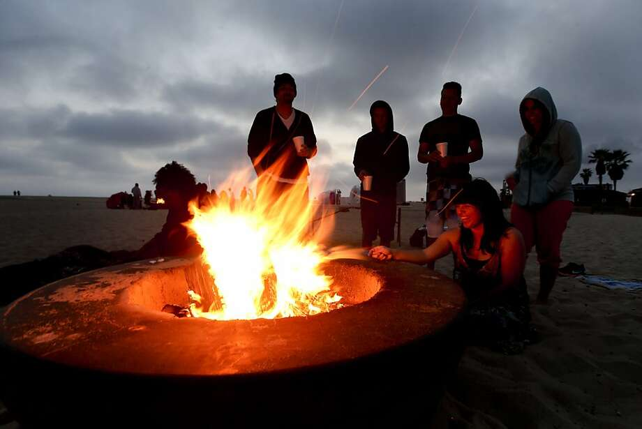 FILE - This April 28, 2012 file photo shows beach goers around a fire pit in Huntington Beach, Calif. Preliminary testing shows that wood smoke from beach bonfires that dot the Southern California coastline is hurting air quality near the fire pits and in adjacent neighborhoods, according to a report, Wednesday May 15, 2013. (AP Photo/Chris Carlson, File) Photo: Chris Carlson, Associated Press