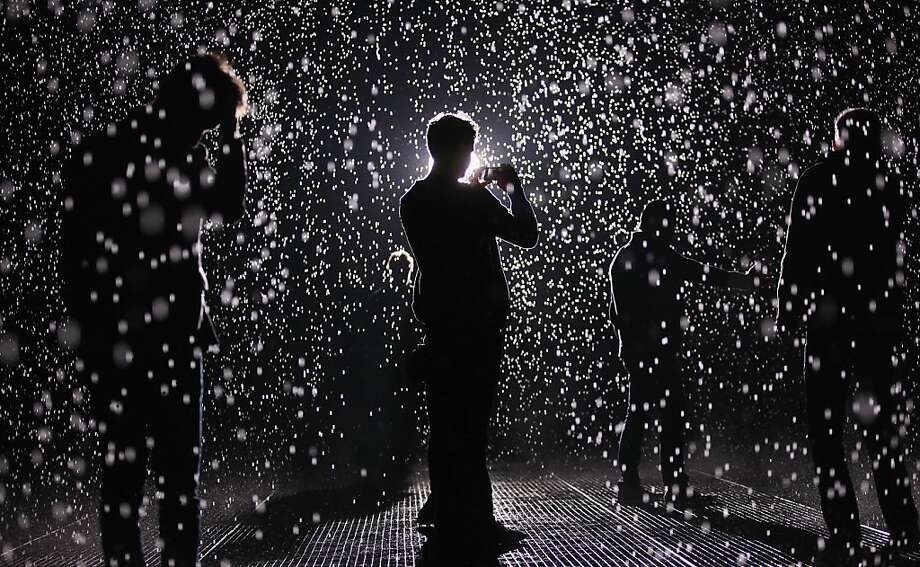 NEW YORK, NY - MAY 15:  Visitors gather in the new 'Rain Room' installation at the Museum of Modern Art (MoMA) in Manhattan on May 15, 2013 in New York City. The 5,000 square-foot installation creates a field of falling water that stops in the area where people walk through, allowing them to remain dry. The piece, created by Random International, releases a 260-gallon per minute shower around visitors.  (Photo by Mario Tama/Getty Images) Photo: Mario Tama, Getty Images