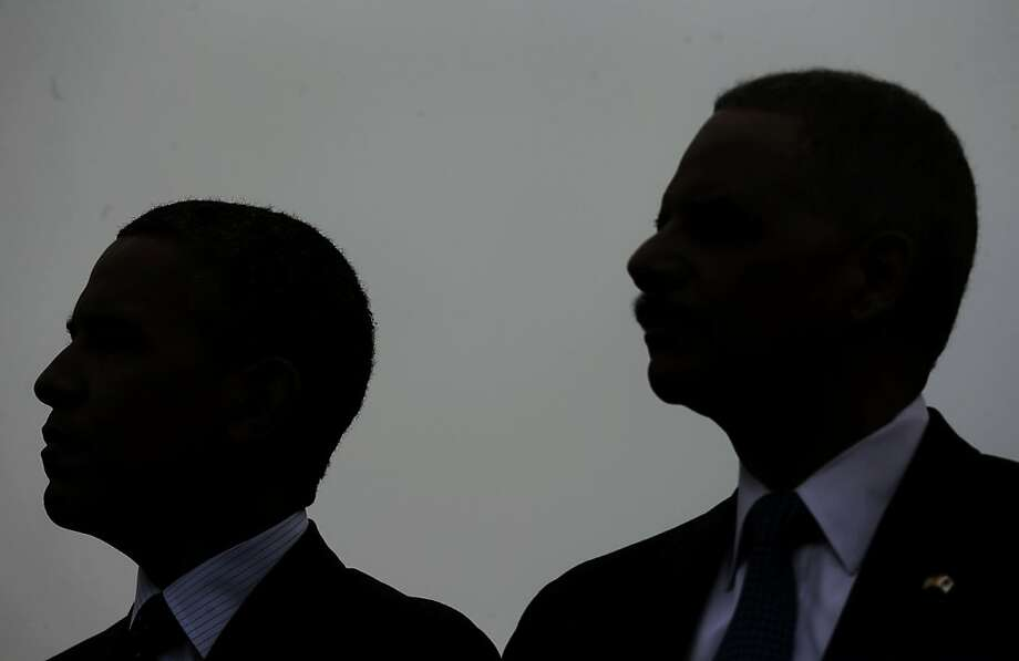 President Barack Obama, left, and Attorney General Eric Holder, right, are silhouetted as they sit on stage together at the National Peace Officers Memorial Service on Capitol Hill in Washington, Wednesday, May 15, 2013, honoring law enforcement officers who died in the line of duty. (AP Photo/Pablo Martinez Monsivais) Photo: Pablo Martinez Monsivais, Associated Press