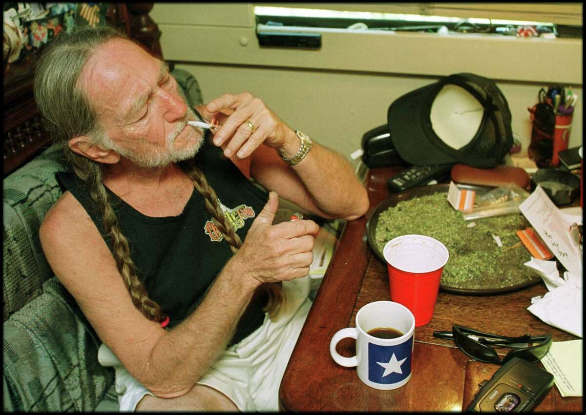 American country singer Willie Nelson takes a drag off a joint while relaxing at his home in Texas, 2000s. A large amount of marijuana is spread out on the table before him