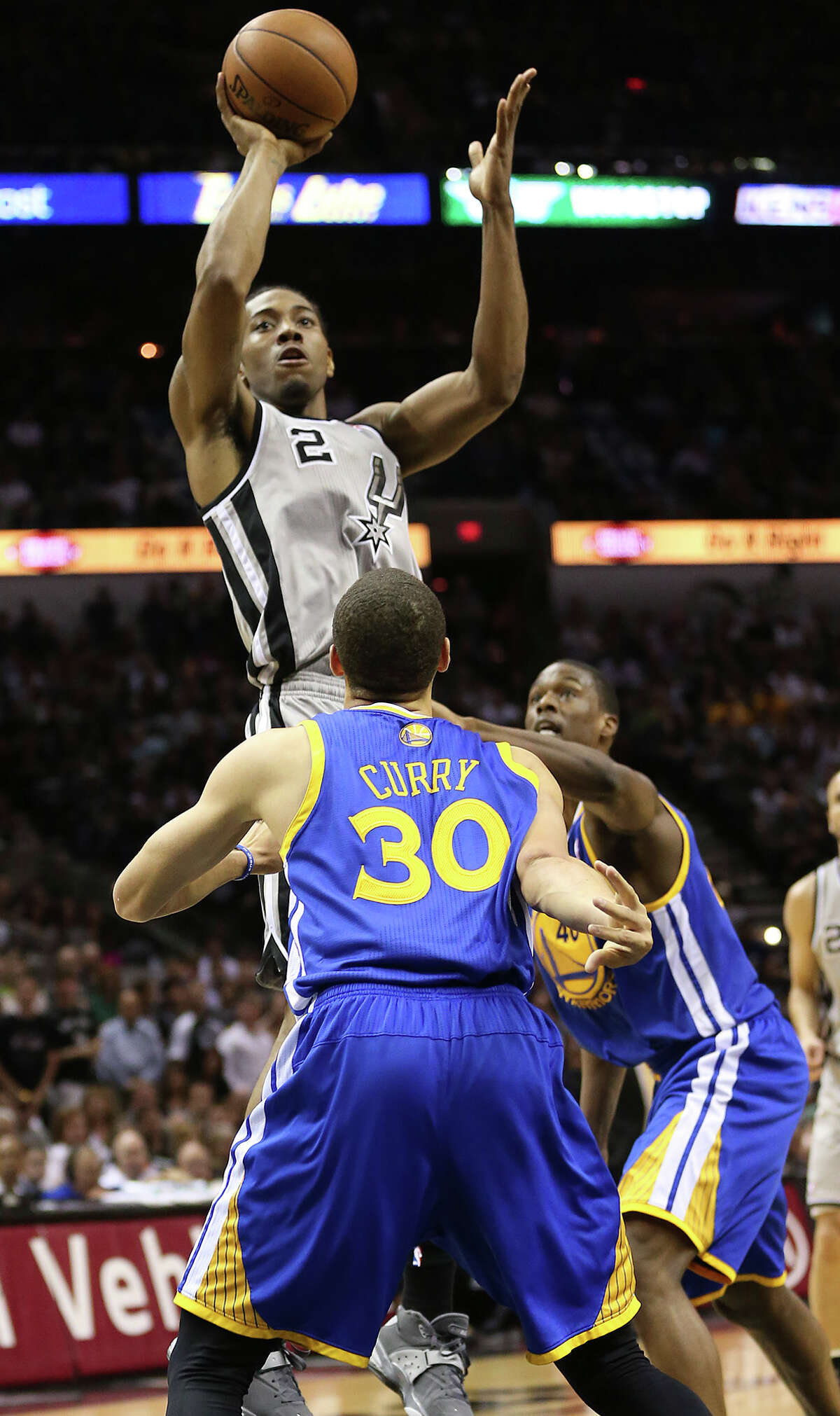 San Antonio Spurs' Kawhi Leonard shoots over Golden State Warriors' Stephen Curry and Harrison Barnes during the first half of Game 5 in the NBA Western Conference semifinals at the AT&T Center, Tuesday, May 14, 2013.