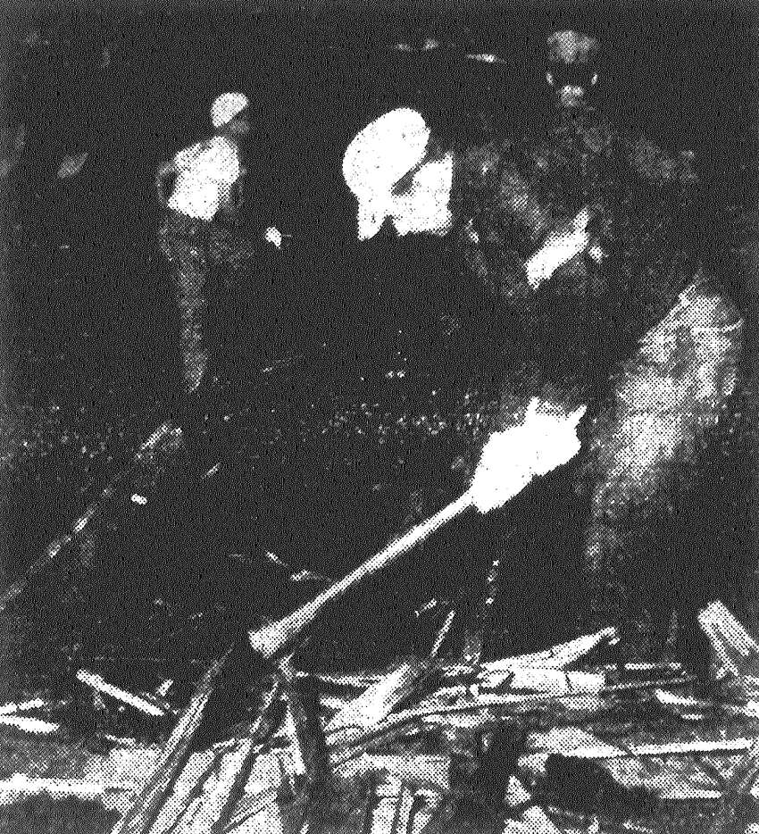 Volunteer servicemen chop away timbers of the R.T. Dennis Building in Waco, clearing a path to search for survivors. Published in the San Antonio Express May 13, 1953.