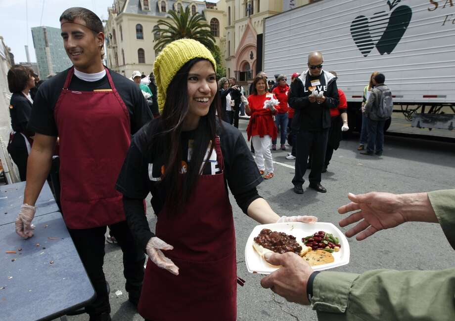 Colleen Javier and Michael Martin (left) distribute lunches where community organizations and city emergency management agencies serve 6,000 hot meals to Tenderloin residents on Golden Gate Avenue to simulate a neighborhood response after a projected 7.8 magnitude earthquake in San Francisco, Calif. on Wednesday, May 15, 2013.