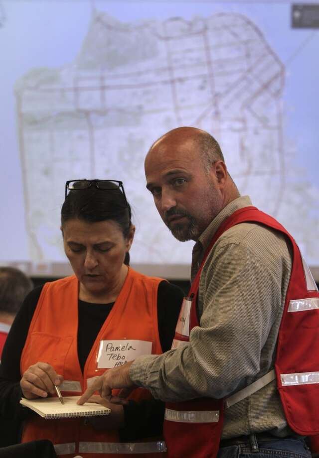 Pamela Tebo and John Murray coordinate the response from the Human Services department during a simulated disaster drill at the Emergency Operations Center after a projected 7.8 magnitude earthquake in San Francisco, Calif. on Wednesday, May 15, 2013.