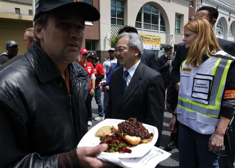 Mayor Ed Lee observes the free meal distribution with incident commander Cissie Bonini (right) where community organizations and city emergency management agencies served 6,000 hot lunches to Tenderloin residents on Golden Gate Avenue to simulate a neighborhood response after a projected 7.8 magnitude earthquake in San Francisco, Calif. on Wednesday, May 15, 2013.
