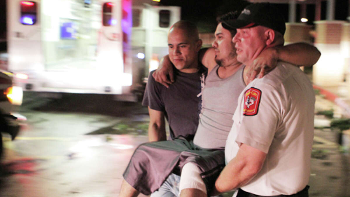 """Johnny Ortiz, left, and James South, right, carry Miguel Morales, center, who was injured in a tornado, to an ambulance in Granbury, Texas, on Wednesday May 15, 2013. Officials report the tornado caused """"multiple fatalities"""" as it tore through two neighborhoods of a North Texas town. Hood County sheriff's Lt. Kathy Jiveden reported the multiple fatalities, but she had no estimate of dead or injured."""