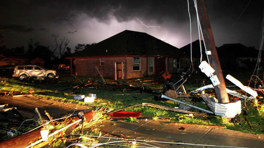 Lightning strikes from a storm illuminates the sky where damage is strewn about the street and light pole near Hyde Park Lane at Country Club Rd. after a tornado in Cleburne, Texas, Wednesday night, May 15, 2013. Cleburne Mayor Scott Cain early Thursday declared a local disaster as schools canceled classes amid the destruction. (AP Photo/The Dallas Morning News, Tom Fox)  MANDATORY CREDIT; MAGS OUT; TV OUT; INTERNET USE BY AP MEMBERS ONLY; NO SALES Photo: Tom Fox, . / The Dallas Morning News