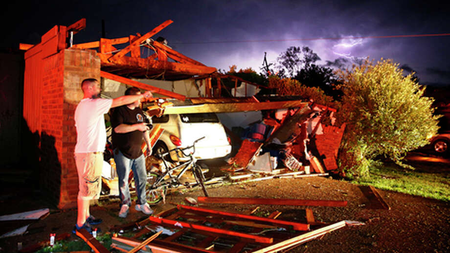 Derrek Grisham, left, points out neighborhood damage to storm chaser Travis Schafer after a tornado damaged his mother's house on Hyde Park Lane at Country Club Rd. in Cleburne, Texas,Wednesday night, May 15, 2013. Cleburne Mayor Scott Cain early Thursday declared a local disaster as schools canceled classes amid the destruction. (AP Photo/The Dallas Morning News, Tom Fox)  MANDATORY CREDIT; MAGS OUT; TV OUT; INTERNET USE BY AP MEMBERS ONLY; NO SALES Photo: Tom Fox, . / The Dallas Morning News