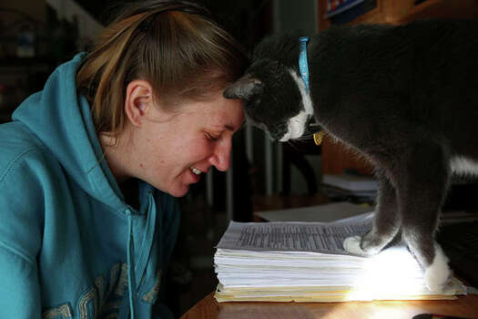 Anna Moore gets a head butt from Morgie the cat, who's stepping on a pile of documents concerning the assault. Included in the papers are the results of Moore's psychiatric exam. Photo: Lisa Krantz / San Antonio Express-News