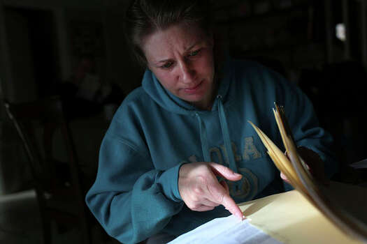 Anna Moore looks through documents concerning her attack and its aftermath at her home in Colorado Springs, Colo. Photo: Lisa Krantz / San Antonio Express-News