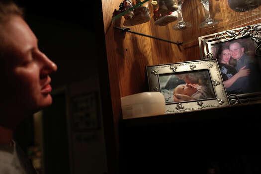 Anna Moore looks over photos of her family. Photo: Lisa Krantz, San Antonio Express-News / San Antonio Express-News