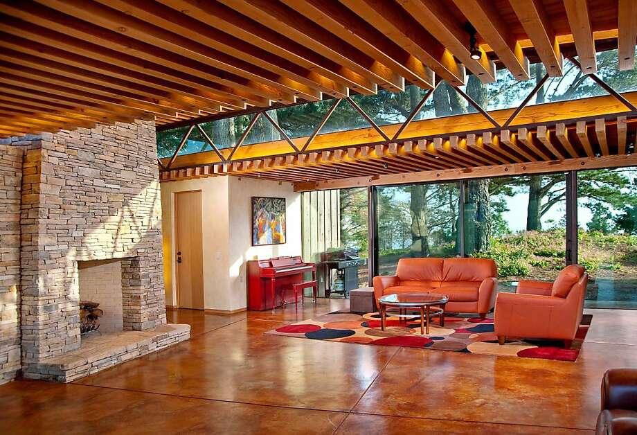 36296 Highway 1 features walls of glass, a stone fireplace and concrete floors. Photo: John Saar