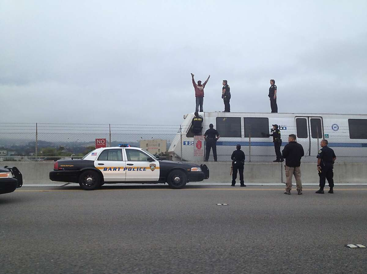 A man is captured by BART police as he stands on top of a BART train just north of the MacArthur Station in Oakland along Interstate 580 on Thursday, May 16, 2013.