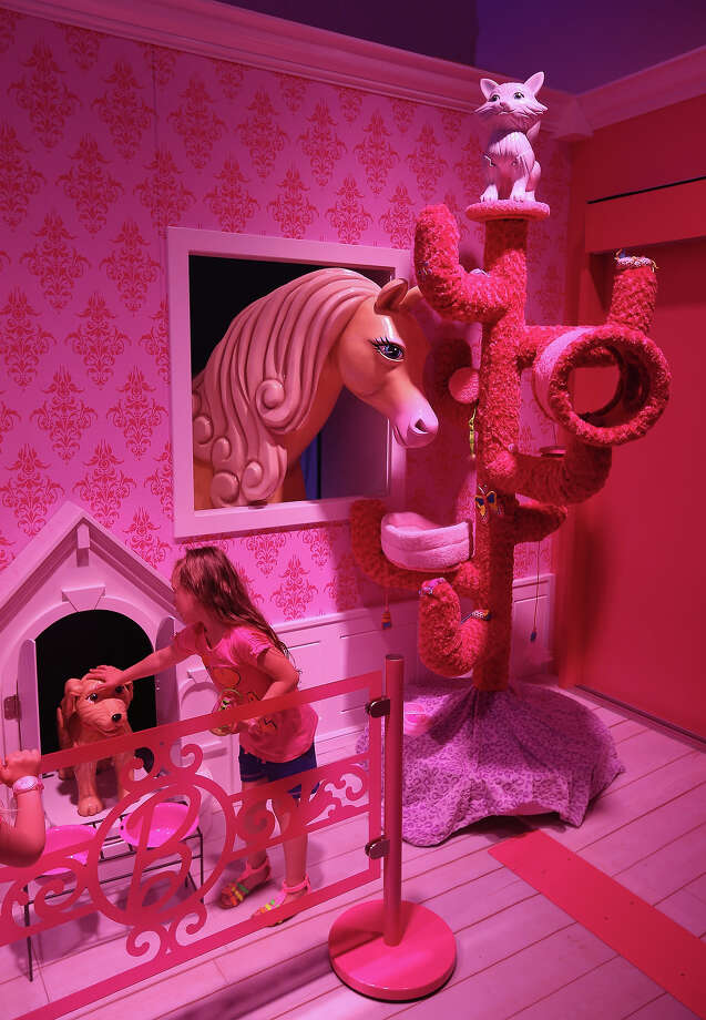 Luna, 6, pets a plastic dog that emerged from his doghouse at the Barbie Dreamhouse Experience on May 16, 2013 in Berlin, Germany. The Barbie Dreamhouse is a life-sized house full of Barbie fashion, furniture and accessories and will be open to the public until August 25 before it moves on to other cities in Europe. Photo: Sean Gallup, Getty Images / 2013 Getty Images