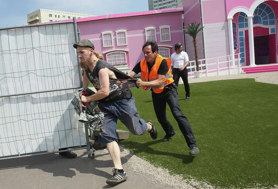 A security guard attempts to restrain a protester who had dunked a burning cross with a Barbie doll attached to it into a fountain outside the Barbie Dreamhouse Experience following a FEMEN protest on May 16, 2013 in Berlin, Germany. The Barbie Dreamhouse is a life-sized house full of Barbie fashion, furniture and accessories and will be open to the public until August 25 before it moves on to other cities in Europe. Photo: Sean Gallup, Getty Images / 2013 Getty Images