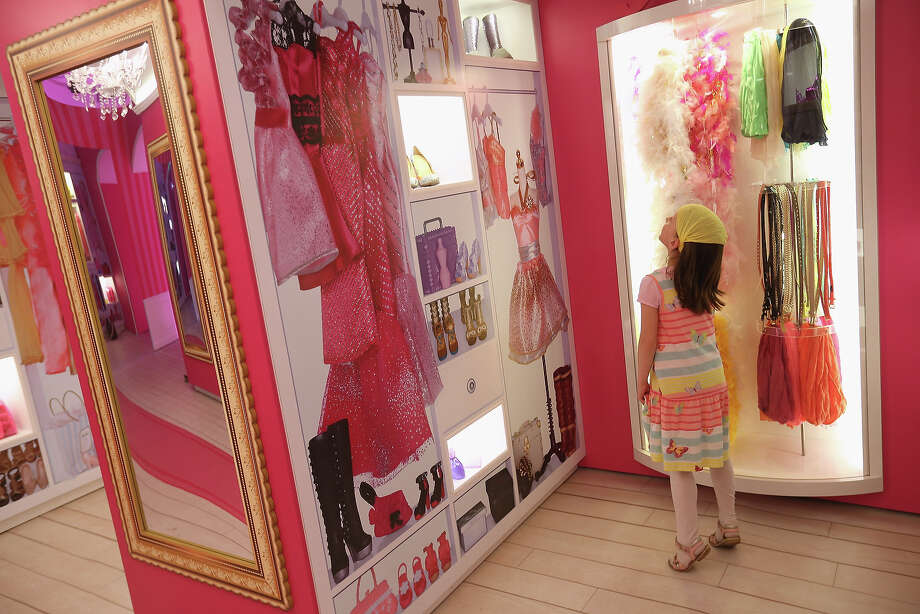 Amalie, 7, looks at items in Barbie wardrobe while visiting the Barbie Dreamhouse Experience on May 16, 2013 in Berlin, Germany. The Barbie Dreamhouse is a life-sized house full of Barbie fashion, furniture and accessories and will be open to the public until August 25 before it moves on to other cities in Europe. Photo: Sean Gallup, Getty Images / 2013 Getty Images