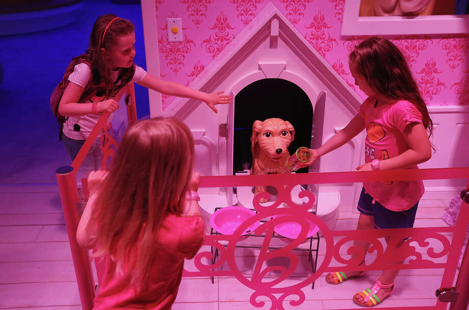 Lara (L), Josi and Luna, all 6, pet a plastic dog that emerged from his doghouse at the Barbie Dreamhouse Experience on May 16, 2013 in Berlin, Germany. The Barbie Dreamhouse is a life-sized house full of Barbie fashion, furniture and accessories and will be open to the public until August 25 before it moves on to other cities in Europe. Photo: Sean Gallup, Getty Images / 2013 Getty Images