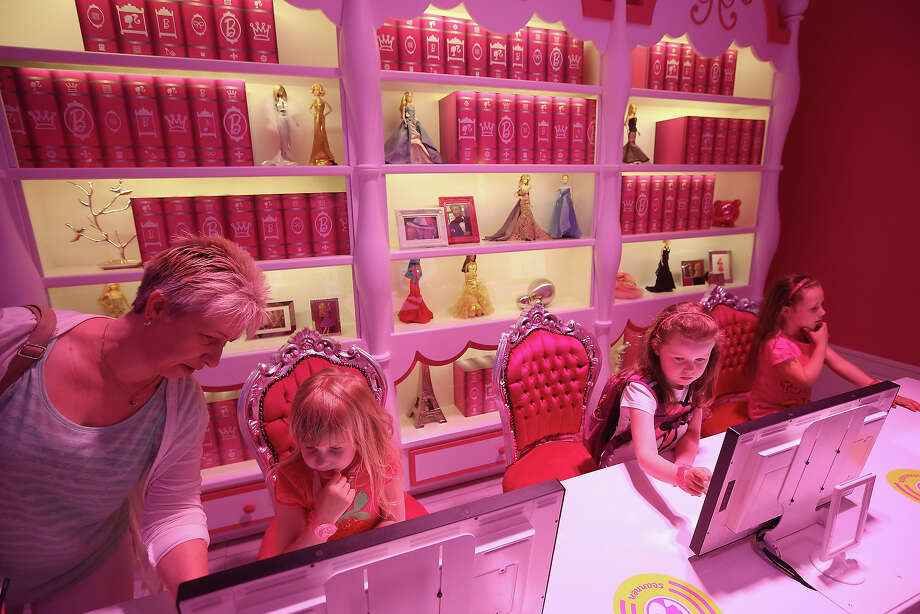 Josi (L), Lara (C) and Luna, all 6, try out computer terminals in Barbie's library at the Barbie Dreamhouse Experience on May 16, 2013 in Berlin, Germany. The Barbie Dreamhouse is a life-sized house full of Barbie fashion, furniture and accessories and will be open to the public until August 25 before it moves on to other cities in Europe. Photo: Sean Gallup, Getty Images / 2013 Getty Images
