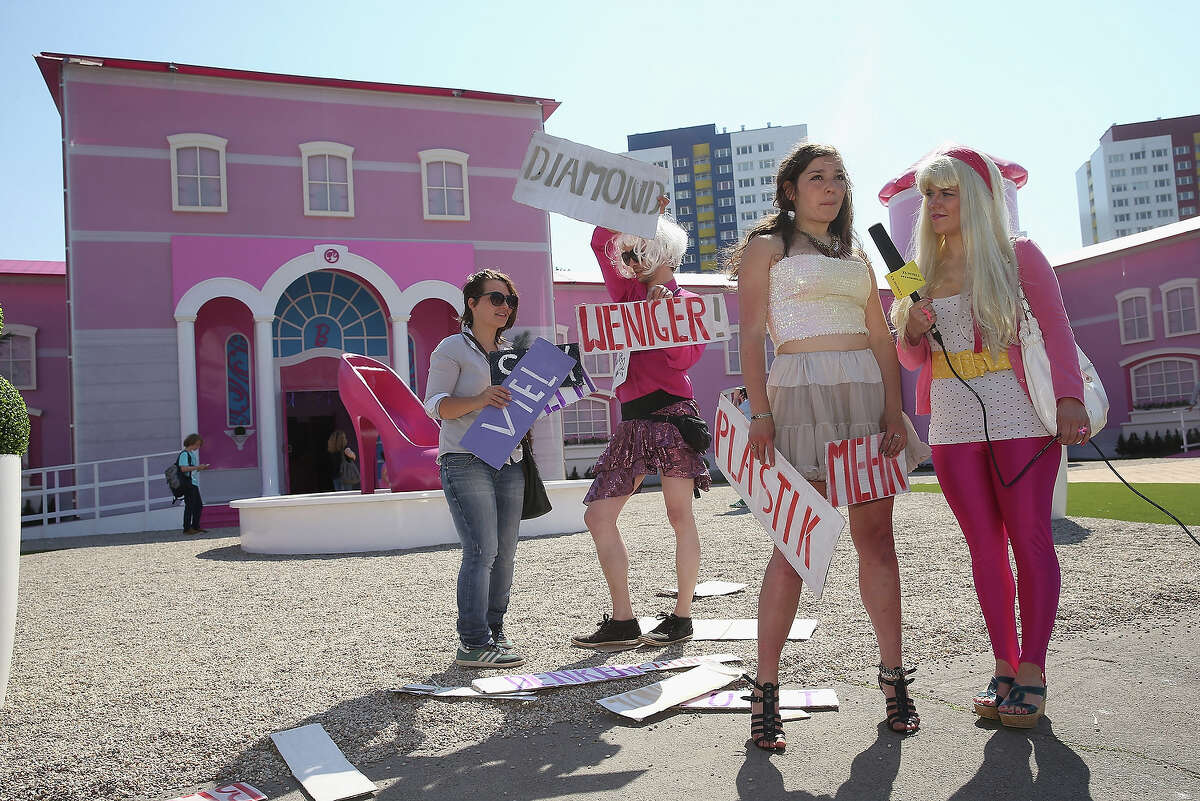 Protesters demonstrating against materialist stereotypes of women are interviewed by a television reporter outside the Barbie Dreamhouse Experience on May 16, 2013 in Berlin, Germany. The Barbie Dreamhouse is a life-sized house full of Barbie fashion, furniture and accessories and will be open to the public until August 25 before it moves on to other cities in Europe.
