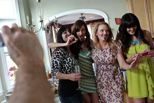 Elle Helmer poses with friends including Jennifer Saucier, from left, Rachel Brysacz, and Nicole Colligan, to show off their fake mustaches during the Easter party at her home in Wilmington, NC on March 31, 2013. Photo: Lisa Krantz / San Antonio Express-News