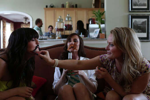 Elle Helmer, right, and her friends, Nicole Colligan, left, and Rachel Brysacz entertain themselves with fake mustaches at her home in Wilmington, NC on March , 2013. Brysacz is a veteran of the Air Force. Photo: Lisa Krantz / San Antonio Express-News