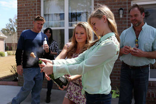 Elle Helmer helps her friends' daughter pop a cork off a bottle of champagne during an Easter party at her home in Wilmington, NC on March 31, 2013. Photo: Lisa Krantz / San Antonio Express-News