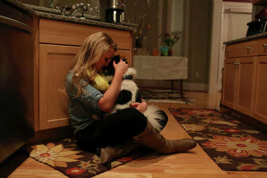 Elle Helmer embraces her dog, Bucky, after going out to dinner with her husband, at her home in Wilmington, NC on March 29, 2013. Photo: Lisa Krantz / San Antonio Express-News