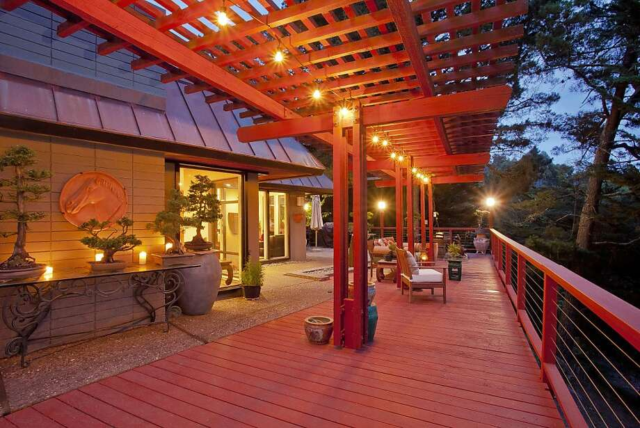 The deck is partially covered and looks out at mature trees. Photo: OpenHomesPhotography.com