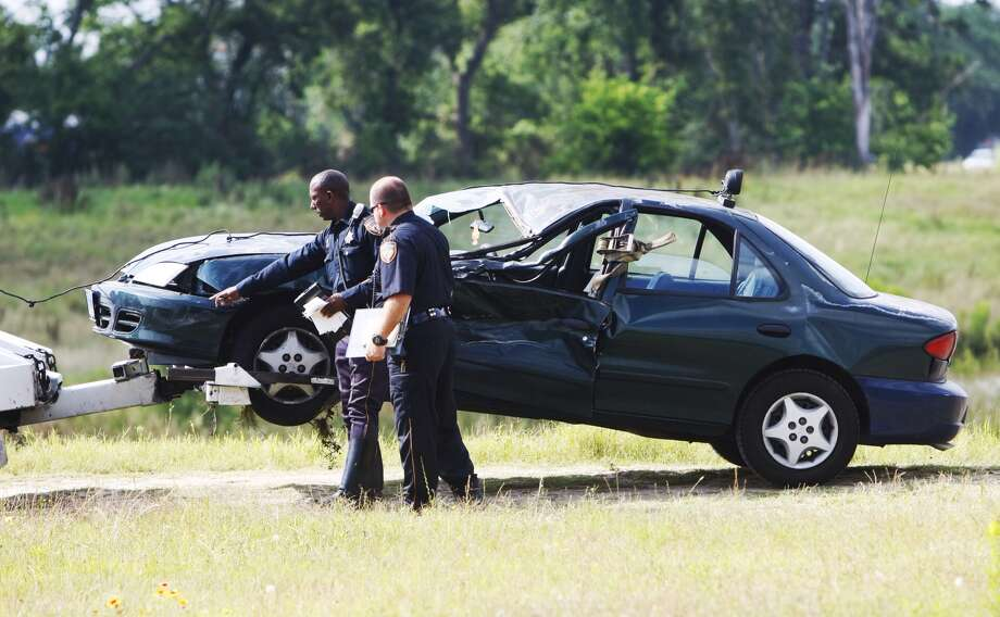 Authorities look at a car after it was found crashed near a retention pond in northwest Houston, May 16, 2013.