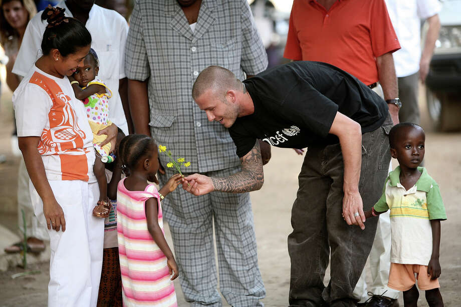 UNICEF Goodwill Ambassador David Beckham (2nd R) is greeted by five-year-old Senyo, who suffers from malnutrition, with yellow flowers upon his arrival at a therapeutic feeding centre as Foday, 5, who is also malnourished, stands beside him on January 19, 2008 in Makeni, Sierra Leone. Photo: David Turnley / 2008 David Turnley