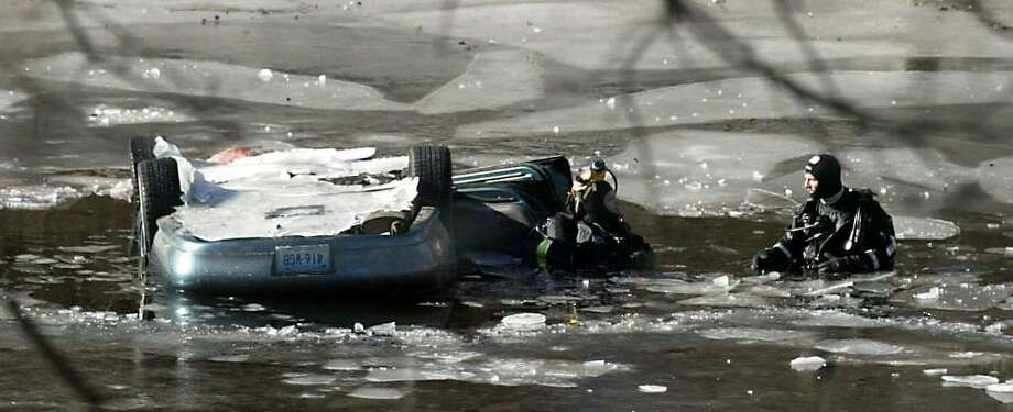 After pulling a body from a car, Bridgeport Police divers survey the scene in the Pequonnock River, Sunday afternoon in Bridgeport. Sunday, Jan. 10, 2010. Photo: Phil Noel / Connecticut Post