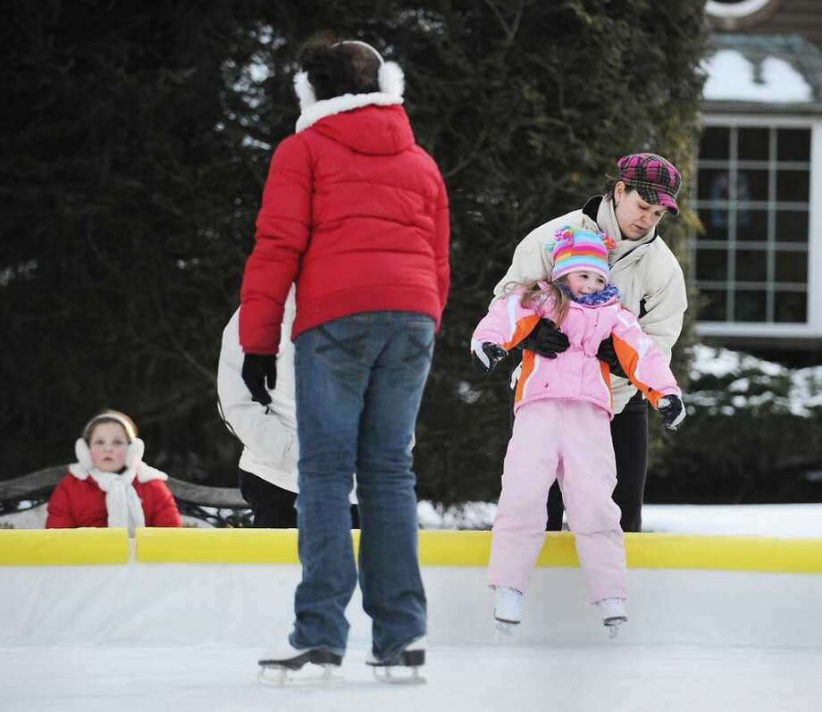 Suzanne DelCarmine lifts her 5-year-old daughter, Taylor DelCarmine, onto their home skating rink in the front yard of their North Stamford home, Sunday,  Jan. 10th, 2010. Photo: Bob Luckey / Stamford Advocate