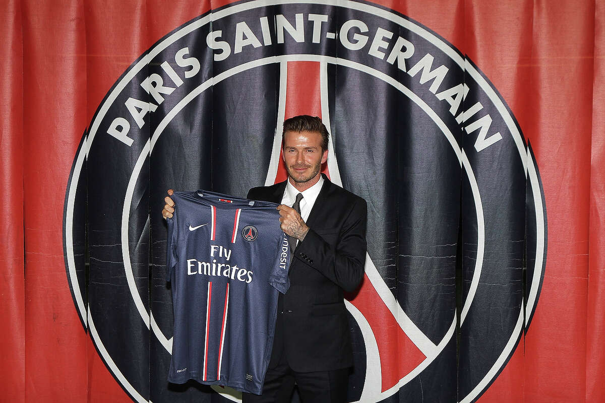 International soccer player David Beckham poses with his PSG Football shirt after his PSG signature at Parc des Princes on January 31, 2013 in Paris. Beckham has announced he is retiring from soccer at the end of this season.