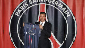 International soccer player David Beckham poses with his PSG Football shirt after his PSG signature at Parc des Princes on January 31, 2013 in Paris.