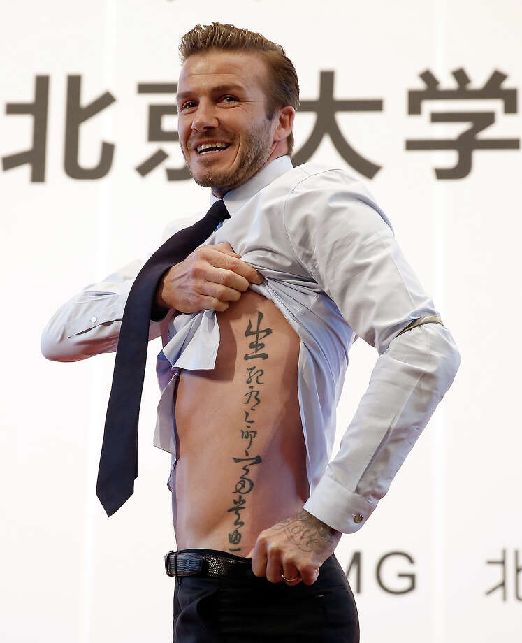 British football player David Beckham shows his tattoo to fans during his visit to Peking University on March 24, 2013 in Beijing, China. David Beckham is on a five-day visit to China at the invitation of the China Football Association as China's first international ambassador. Photo: Lintao Zhang, Getty Images / 2013 Getty Images